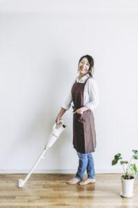 コードレス掃除機をかける女性