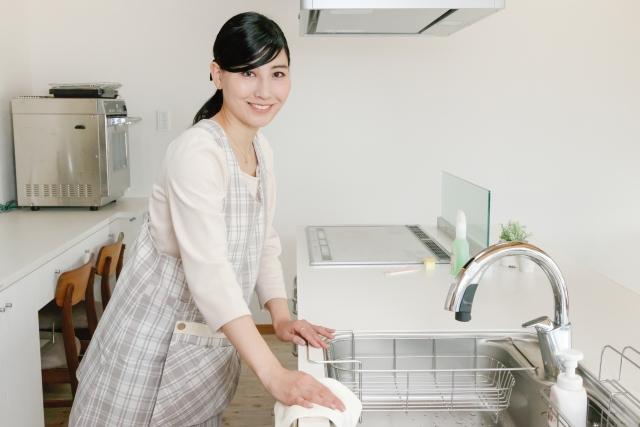 キッチンの汚れをすぐに拭き取る女性